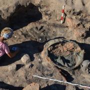 Browar lub kuchnia średniowieczna osady zawierające piecowisko z brązowym kotłem i zestawem akcesoriów (narzędzia żelazne, rożen